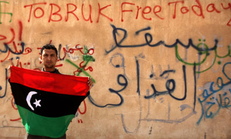 A Libyan anti-government protester holds a flag in Tobruk. Photograph: AFP/Getty Images //The Guardian